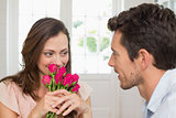 Woman looking at man with flowers at home