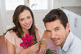 Happy young couple with flowers at home