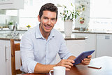 Smiling man using digital tablet at home