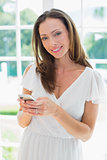Smiling woman text messaging in home