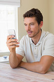 Concentrated man text messaging in home
