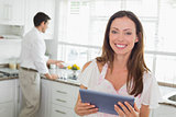 Woman using digital tablet with man in background in kitchen