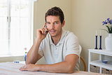 Relaxed man using mobile phone at home