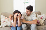Man consoling a sad woman in living room