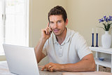 Smiling man using laptop and mobile phone at home