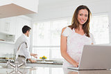 Woman using laptop with man in background in kitchen