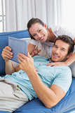 Loving couple with digital tablet in living room