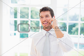 Smiling businessman using mobile phone at home