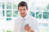 Smart smiling businessman text messaging