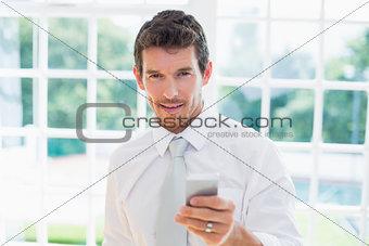Smart smiling businessman text messaging