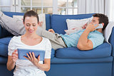 Couple using digital tablet and cellphone in living room