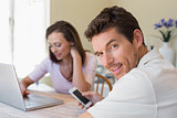 Couple using laptop and cellphone at home