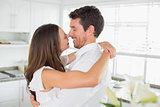 Loving young couple embracing in kitchen