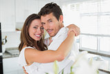 Loving young couple embracing at home