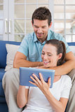 Happy couple using digital tablet on couch