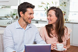 Couple using digital tablet while having coffee at home