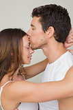 Loving man kissing woman on forehead at home