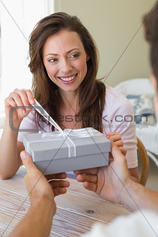 Cropped man giving happy woman a gift box