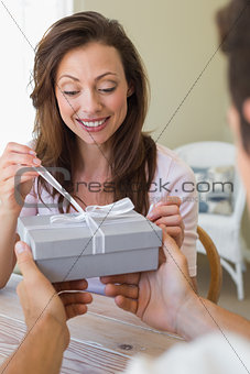 Cropped man giving woman a gift box at home