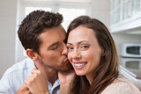 Loving man kissing woman on cheek at home