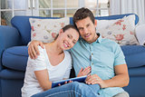 Happy couple using digital tablet in living room