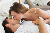 Relaxed couple kissing in bed