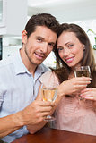 Happy loving couple with wine glasses at home