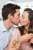 Loving couple with wine glasses kissing at home