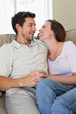 Cheerful relaxed couple sitting on couch