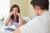 Upset young woman and man with home bills
