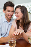 Happy woman showing engagement ring besides man