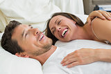 Cheerful couple lying together in bed