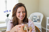 Smiling woman toasting wine glass at home