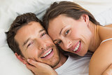 Happy young couple lying together in bed