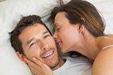 Cheerful young couple lying together in bed