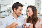 Happy couple with coffee cups in kitchen