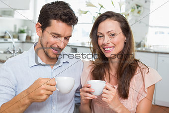 Happy young couple with coffee cups in kitchen