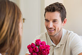 Happy man looking at woman with flowers