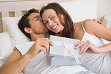 Relaxed couple with gift box lying together in bed