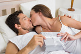 Couple kissing with gift box in hand in bed