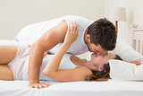 Relaxed young couple kissing in bed