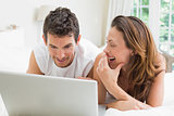 Happy couple using laptop in bed
