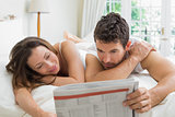 Couple reading newspaper in bed