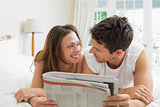 Relaxed couple reading newspaper in bed