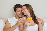 Happy relaxed couple with orange juice in bed