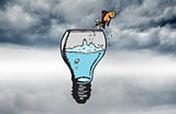 Composite image of goldfish jumping from light bulb bowl