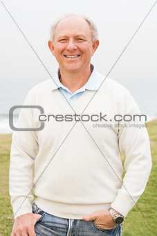 Smiling aged man on grass land background