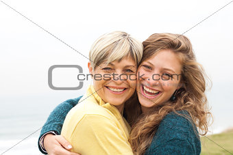 Happy mother and daughter looking at camera