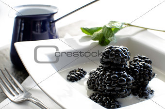 Bowl of fresh blackberries and milk.
