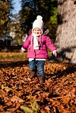 cute littloe girl playing outdoor in autumn